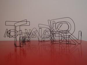 Letters van metaaldraad vormen woorden die weer in elkaar gevlochten zijn,